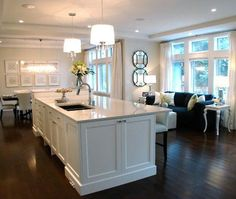 Gorgeous open kitchen design! White drum pendant kitchen island lights, white granite counter tops, white kitchen island, dark espresso wood floors and parson counterstools barstools. soft gray beige walls paint color.