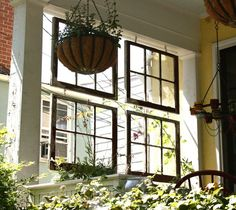 "Vintage windows hung from chains to create a ""window wall"" along the side of a porch. recycledluxury"