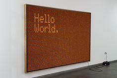 Hello World. Die Installation von Valentin Ruhry besteht aus 5.000 beleuchteten Schaltern, die mit elektrischem Strom versorgt und wie ein großes Gemälde arrangiert wurden. Die spielerischen Möglichkeiten sind großartig und mehr oder weniger umgehend entsteht der Drang, eine eigene Botschaft in das Kunstwerk zu knipsen.