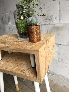 Een close up van het ontwerp van Arjen: tafeltje van OSB met doorgestoken pootjes, eiken omlijsting en zwart rubberen ringen om de poten op hun plek te houden / A close up of the small side table with legs going straight through the OSB wood, with oak framework and black rubber rings to hold the legs in place. Design by Arjen for 'De zussen van zelf'.
