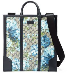 """Gucci GG Blooms North-South Tote, Blue - Gucci tote bag in GG supreme canvas with blue blooms print. Black leather trim. Double leather tote handles; 4"""" drop. Removable and adjustable black nylon strap with leather shoulder pad; 23.5"""" drop. Open top. Gusseted sides; center zip compartment. Interior zipper and smartphone pockets. Alcantara fabric lining with suede-like finish. 15.5""""H x 14.5""""W x 4.5""""D. Made in Italy."""