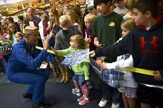 Lt. Cmdr. John Hiltz, right wing pilot number 2, of the U.S. Navy flight demonstration squadron, the Blue Angels, gives a high five to a girl at the National Naval Aviation Museum at Naval Air Station Pensacola, Fla.