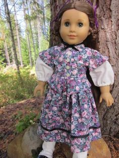 American Girl dolls, Cecile, Marie Grace and Addy will love this beautiful peplum- style day dress! It is made from 100% quilters cotton in a floral print featuring pink and purple flowers and grey-green leaves on a black background. The sleeves and collar are white cotton. The