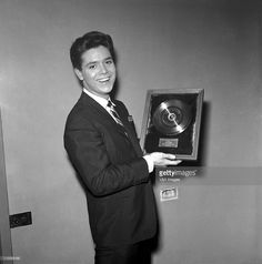 Cliff Richard, posed, with first gold record, 1959.