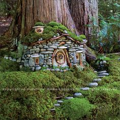 Stone fairy house at the base of a tree with stone walkway and roof covered in moss. Fairy Tree Houses, Fairy Village, Fairy Garden Houses, Gnome Garden, Garden Art, Garden Design, Gnome Village, Woodland Garden, Gnome House