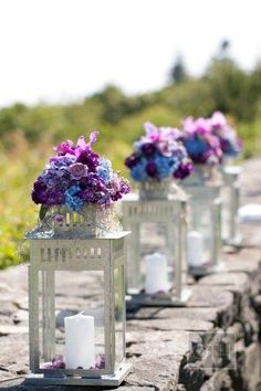 This site has a ton of beautiful flower ideas!  I love the bunches of blue and purple flowers on top of lanterns as wedding centerpieces! #wedding #lanterns