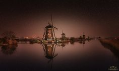 Dutch Pride - Typical Kinderdijk night scenery with the right conditions. Nice calm water and great reflections. This image was made out of 2 exposures. The sky and stars (late at night, high ISO) were blended in afterwards..................