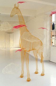 Coloured steel mesh sculpture of tall freestanding giraffe by Benedetta Mori Ubaldini