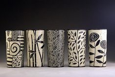 Cylinder Vases by Jennifer Falter. Wheel thrown porcelain vases with whimsical designs: patches, bamboo, doodle, branch and leaf, and roses. The surface of each vase is hand carved through a layer of black slip to create a contrasting and textural surface, using a technique known as sgraffito. Each piece is unique. Size and design may vary slightly from image shown. Signed on the bottom. Dishwasher safe.