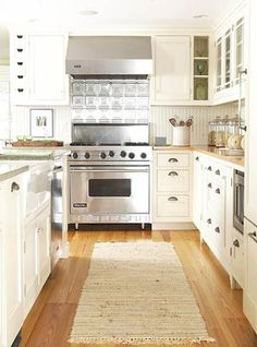 Old-fashioned backsplash surfaces -- tin for the range and beaded board elsewhere -- convey vintage charm. Recessed lighting illuminates work spaces.