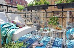garde-corps en fer, canapé droit métallique, tapis ethnique et table appoint assortie
