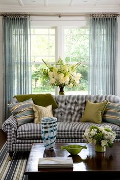 Living room with a tufted, black and white gingham sofa, striped rug, sheer gingham curtains and a wood coffee table