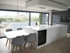 dining table off large kitchen island with grey and white units, herringbone wooden floor and large slider doors to patio