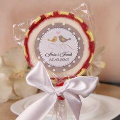 Tradycyjne lizaki owocowe o średnicy 55 - 58 mm zawinięte w przezroczystą folię, oklejone etykietami z nadrukowanymi motywami ślubnymi oraz przewiązane gustownymi kokardkami w kilku kolorach.