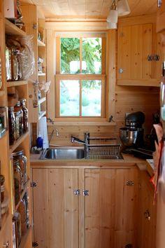 A tiny home kitchen with storage all around the window Tiny