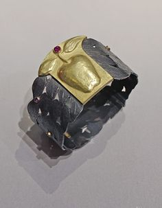 """Linda Kindler Priest: Delicious Apple Bracelet, Hinged bracelet in 14k yellow gold, 88pt rubies, and oxidized sterling silver with clasp. 1 - 1 1/2"""" wide."""