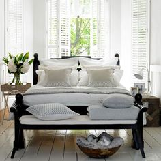 Relaxed neutral bedroom - Dark-wood furniture against the white walls