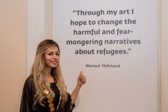 Artist Wurood Mahmood smiles next to her words. Photo credit: Mahmood Mahmood