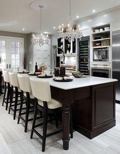 large kitchen island / table / chandeliers / tall wine fridge / white washed hardwood floors