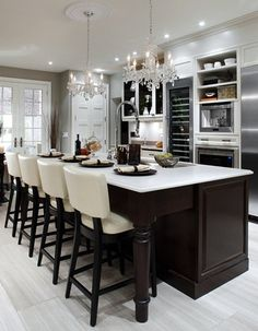 large kitchen island / table / chandeliers / tall wine fridge / white washed hardwood floors