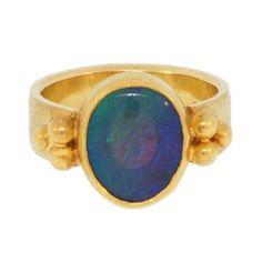 Black Opal Byzantine Ring by Linelle Lynch  United States  20th Century  This elegant ring is a handmade creation by Linelle Lynch and features a 3.60 ct natural black crystal opal from Lightning Ridge, Australia set it in a 22kt bezel on a 0.24 inch (6.2 mm) wide 18kt ring with bold 22kt granulation. The ring has an acid depleted finish with a lightly hand hammered edge and is presently a size 71/2. The opal has soft green and blue play of color reminiscent of the Caribbean.