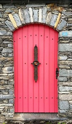 Unique pink door with surrounding stonework in Brissago, Ticino, Switzerland.