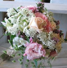 Beautiful bouquet of pale apricot roses, pink lisianthus, white altro, Queen Anne's Lace and Geraldton wax.  http://www.placervilleflowermarket.org/images/flowers/bridalb.four.jpg