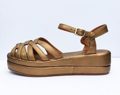 """Flat platform sandal with strappy vamp, padded footbed, and ankle strap. Leather upperswith cushion crepe stylesoles Whole sizes, 5 – 11 Medium widths 1 ⅞"""" we"""