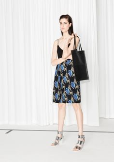 Enchanting water lily print amps up the fluid appeal of this crepe midi skirt with an elegantly pleated front.