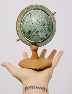 A photo of a man holding out his arm with a small wooden vintage world globe in his hand, with a wrist tattoo of Fernweh and a hand-drawn compass. Photo taken with Canon 650D Rebel T4i and 24-105mm lens, edited with VSCO Film 400+ in Adobe Lightroom.