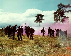 Companies B and C, 1st Bn, 8th Inf, 1st Bde, 4th Infantry Division, assemble on top of Hill 742, located five miles northeast of Dak To, prior to moving out. A purple smoke grenade is ignited in the background to guide in a helicopter, November 14-17. 1967.