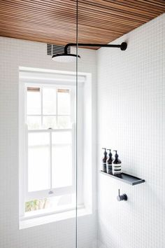White tiles and wood elements feature in this modern bathroom, and a pull-down blind provides privacy without blocking out too much light from the window. /