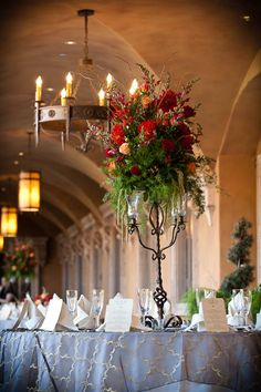 Iron candelabra with red Gerber daisies, orange roses, and cranberry snapdragons | villasiena.cc