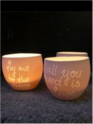 """Thin candle porcelain bowls engraved with """"look through"""" sentences."""
