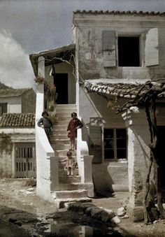 Girls-stand-on-a-stairway-of-a-house-in-a-Greek-fishing-village-Benizze-Corfu- | da janwillemsen