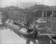 """Captioned: """"25th April 1917: A motor coal barge on Regent's Canal unloading its cargo."""" #Regents #Canal # London #Boat #lighter #barge #dock #east #limehouse #docklands #historic #railway #interchange #wharf #narrowboat #outboard #experiment"""