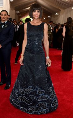 2015 Met Gala: Zac Posen is wearing a midnight blue sleeveless Zac Posen gown with silver flower detail on the bottom and sparkles. Katie also debuts a new do! The dress is exquisite!