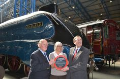 Mallard locomotive, April 2013. Sir Nigel Gresley's grandson, Tim Godfrey; Helen Ashby, Head of Knowledge & Collections at the National Railway Museum and John Wood, Chairman of the Institution's Engineering Heritage Committee pose in front of Mallard locomotive.