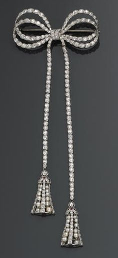 A diamond, cultured pearl and ruby pendant-brooch  of double bow design, its terminals set throughout with European and transitional-cut diamonds, suspending tassels of round graduated pearls, square-cut rubies, and single-cut diamonds; estimated total diamond weight: 3.15 carats; mounted in platinum.