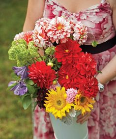 """Come midsummer the farmers' market is brimming with fruits, vegetables, and garden-fresh flowers. Picking up a bucket of these seasonal blooms, stylist Paul Lowe devised 10 beautiful — and easy — floral treatments.  For a summer party, he suggests pairing dahlias, clematis, viburnum, chocolate cosmos, chamomile, and eucalyptus berries with vintage containers for a look he calls """"rustic elegance.""""  """"Flowers are versatile,"""" he adds. """"There are so many things you can do."""""""