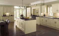 very open plan, pale green coloured kitchen, shaker-style cabinets