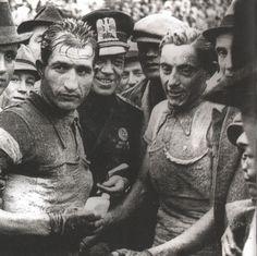 Gino Bartali (1914-2000) e Fausto Coppi (1919-1960) al termine di una competizione. Siamo nel 1941 (o forse nel tardo autunno 1940). Bartali veste la maglia tricolore di Campione d'Italia ed è l'indiscusso numero numero 1 in Italia e nel mondo. Ma il giovane Coppi non nasconde ambizione ed entusiasmo...