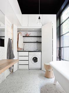 Hidden laundry: white, bifold doors, custom joinery, drawers, black shelves and benchtop, marble diamond mosaic tiles and splashback, Mark Tuckey eggcup stool, glass pendant light