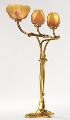 "Louis Majorelle ""MAGNOLIA"" THREE-LIGHT TABLE LAMP one shade engraved DAUM/NANCY and with the Croix de Lorraine gilt bronze and wheel-carved glass, circa 1903, in collaboration with Auguste and Antonin Daum."