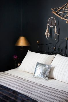I grew up with the antique brass bed and gave it new life with a glossy black paint job from an auto body shop. The wool blanket is a Pendleton and Dwell Studio collaboration, and the bedding is from Coyuchi. The wood art over the bed is from Argentina. I love the earthy meets glam feel of this room.