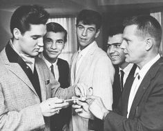Elvis Presley - Elvis gets the key to the city of Hollywood from the Mayor's representative, Lee Brunn. The teenagers also in the photograph apologized to Elvis after throwing eggs and tomatoes at his train when he went through town, c. 1960s.
