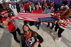 Fans limbo dance under a U.S. flag to celebrate Jamie Anderson's gold medal in the women's snowboard slopestyle final at the 2014 Winter Olympics on Feb. 9, 2014.
