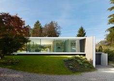 Slideshow: the glazed walls of this pavilion-like house in southern Germany are sandwiched between a roof and plinth that mirror one another (photographs by Zooey Braun). Completed by Stuttgart architects Werner Sobek Design, the ground floor of House D10 is raised just above the surrounding lawn, while a basement floor is concealed beneath. A large