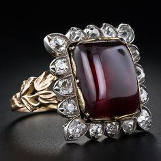 A sizable buff-cut cabochon garnet shimmers and glows from a regal setting, hand crafted in silver over gold, and outlined with one carat of sparkling, deep-cut, antique cushion-cut diamonds. A graceful foliate ring shank completes this early-Victorian, possibly Georgian, beauty. 3/4 of an inch by 11/16 of an inch across.