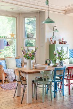 So much to love - mix and match painted chairs, school chair, green cupboard, pendant lamps, checkerboard, light wood
